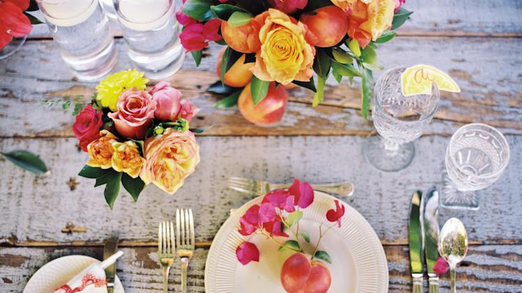 This 2013 publicity photo provided by courtesy of Martha Stewart Living Omnimedia, Inc. shows calligraphed paper lemon wedges, perched on rims of glass goblets, that serve as placecards in place settings from the Real Weddings spread, originally published in the spring issue of Martha Stewart Weddings magazine. Combining rusticity and elegance is a modern trend in wedding receptions.  Flowers can have a less formal presentation, and seating can be more casual. (AP Photo/Martha Stewart Living Omnimedia, Inc.)