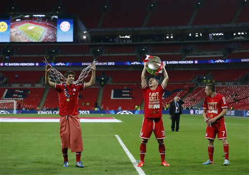 Bayern's Bastian Schweinsteiger with the trophy, celebrates with Bayern's Franck Ribery of France, right and Bayern's Javi Martinez of Spain, left,  after winning  the Champions League Final soccer ma