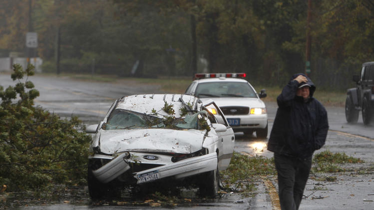 A car crushed by a fallen tree sits along Montauk Highway as Hurricane Sandy approaches, Monday, Oct. 29, 2012, in Bay Shore, N.Y.  Hurricane Sandy continued on its path Monday, forcing the shutdown of mass transit, schools and financial markets, sending coastal residents fleeing, and threatening a dangerous mix of high winds and soaking rain. (AP Photo/Jason DeCrow)