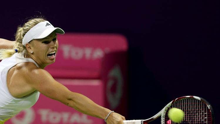 Caroline Wozniacki of Denmark returns the ball during her match against Romania's Sorana Cirstea on the third day of the WTA Qatar Ladies Open in Doha, Qatar, Wednesday, Feb. 13, 2013. (AP Photo/Osama Faisal)