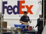 Handlers scan and affix a courier route label onto packages moving down the belt at the Marina Del Rey, California FedEx station December 12, 2011. REUTERS/Fred Prouser