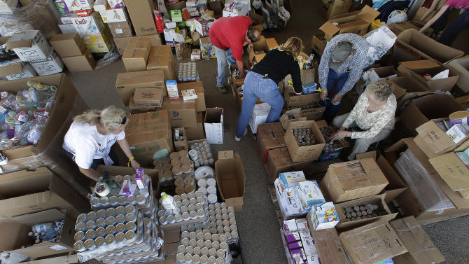 Volunteers sort through goods donated for victims of last week's fertilizer plant explosion Monday, April 22, 2013, in West, Texas. There has been an outpouring of donations for the community in the wake of the massive explosion at the West Fertilizer Co. last Wednesday that killed 14 people and injured more than 160 others. (AP Photo/Charlie Riedel)