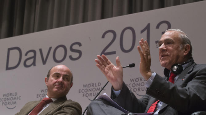 Secretary-General of the OECD, Angel Gurria, right, gestures as he speaks at the Open Forum, while Spanish Economy Minister, Louis de Guindos Jurado looks on, on the sideline of the 43rd Annual Meeting of the World Economic Forum, WEF, in Davos, Switzerland, Friday, Jan. 25, 2013. (AP Photo/Michel Euler)