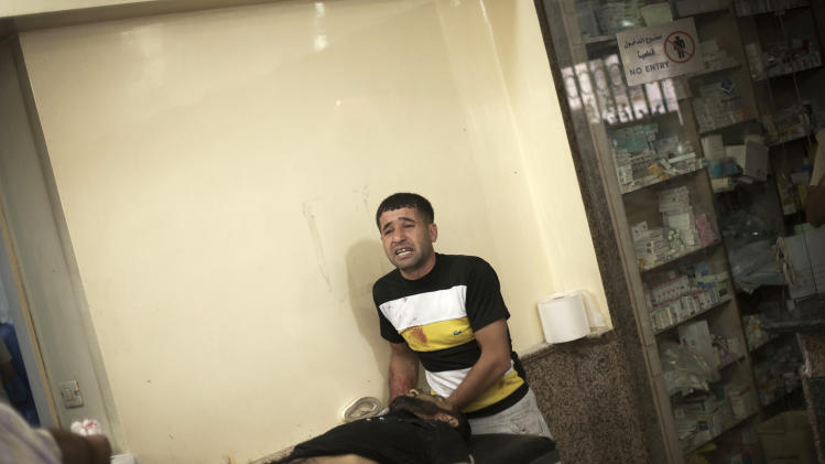 In this Thursday, Oct. 11, 2012 photo, a Syrian man cries while helping his relative wounded by Syrian Army shelling at Dar al-Shifa hospital in Aleppo, Syria. (AP Photo/Manu Brabo)