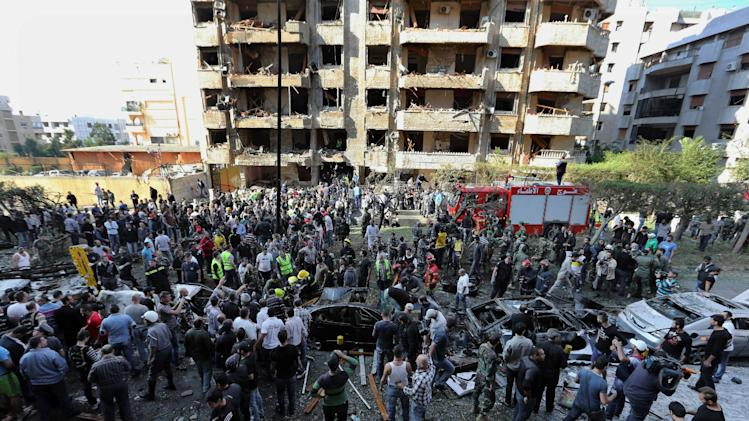 FILE - In this file photo taken Tuesday, Nov. 19, 2013, Lebanese people gather at the scene where two explosions have struck near the Iranian Embassy in Beirut, Lebanon. DNA tests confirmed that a man in Lebanese custody is the suspected leader of an al-Qaida-linked group that has claimed responsibility for bombings across the Middle East, the Lebanese army said Friday, Jan. 3, 2014. The latest attack claimed by the group, the Abdullah Azzam Brigades, was the Nov. 19 double bombing of the Iranian Embassy in Beirut that killed at least 23 people and wounded dozens. (AP Photo/Bilal Hussein, File)