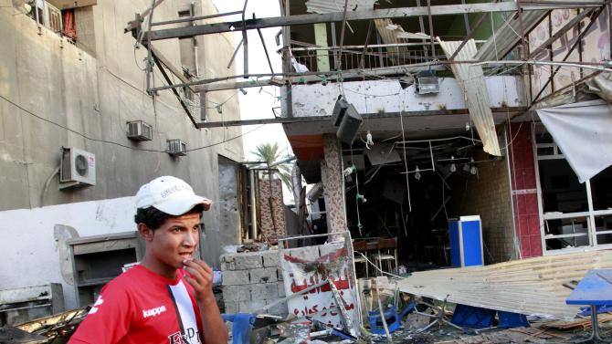 A man inspects the aftermath of a car bomb attack at the Karrada neighborhood of Baghdad, Iraq, Wednesday, Sept. 4, 2013. A series of coordinated evening blasts in Baghdad and other violence killed and wounded scores of people on Tuesday, officials said, the latest in a months-long surge of bloodshed that Iraqi security forces are struggling to contain. (AP Photo/Hadi Mizban)