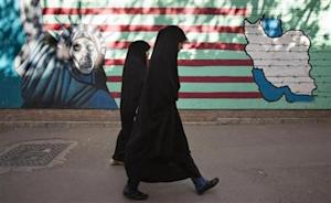 Iranian women walk past an anti-U.S. mural on the wall of the former U.S. embassy in Tehran