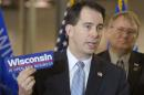 FILE - In this March 17, 2011 file photo Wisconsin Gov. Scott Walker holds a bumper sticker with his signature campaign promise for the state as he announces a new manufacturer will move to Pleasant Prairie, near Kenosha, Wis. Best known for effectively ending collective bargaining in the state and surviving a recall election, the Republican governor's re-election bid is now facing a major campaign issue over something he didn't go. Walker promised in 2010 that over four years the state would add 250,000 private sector jobs: Now three years into his term he's less than halfway there. (AP Photo/Journal Times, Mark Hertzberg, File)