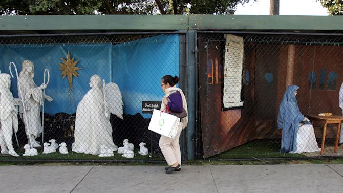 A woman walks past a display showing the Nativity scene along Ocean Avenue at Palisades Park in Santa Monica, Calif.  Tuesday, Dec. 13, 2011.   Most of the Christmas nativity scenes that local churches had placed in a Southern California coastal park for nearly six decades have been displaced by non-believers and the churches say it was a coordinated attack.   But atheists got all but three of the spaces this year because of a new lottery system. The coalition got two spots and one went to Isaac Levitansky of Chabad Channukah Menorah.   (AP Photo/Ringo H.W. Chiu)