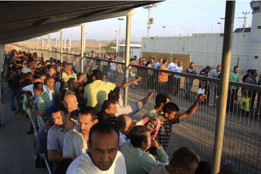 In this Tuesday, Oct. 9 photo, Palestinian workers wait to cross to Israel at the Qalqiliya checkpoint. In response to an economic crisis gripping the West Bank, Israel has suddenly increased the number of permits for Palestinians to work inside Israel. (AP Photo/Nasser Ishtayeh)