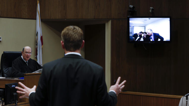 Deputy District Attorney Kurt Mechals, center, speaks as Kassim Alhimidi, right, is seen on a video screen in his video arraignment alongside his attorney, Armando Salazar, right, and an unidentified translator Tuesday, Nov. 13, 2012, in El Cajon, Calif. At left, Judge Herbert Exarhos looks on.  Alhimidi pleaded not guilty to charges that he killed his wife, Shaima Alawadi, last March. 1(AP Photo/Gregory Bull)