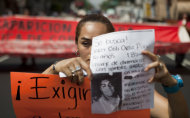 A woman holds up a sign with details of her recently disappeared relative during a protest in Mexico City, Thursday, May 30, 2013. Eleven young people were kidnapped in broad daylight from a Mexico City bar, just 20 days after the grandson of civil rights leader Malcolm X was beaten to death at a nightclub in the capital, anguished relatives said Thursday. (AP Photo/Eduardo Verdugo)