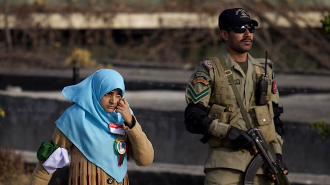 A supporter of Pakistani cleric Tahir-ul-Qadri walks past a soldier during a rally in Islamabad, Pakistan, Monday, Jan. 14, 2013. Thousands of supporters of a fiery cleric who has been calling for election reforms were descending Monday on the Pakistani capital, where authorities have put up barricades and sent riot police into the streets in preparation. (AP Photo/B.K. Bangash)