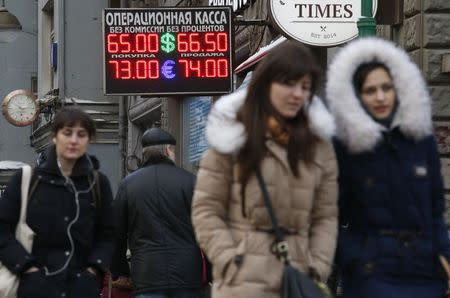People walk past a board showing currency exchange rates in Moscow