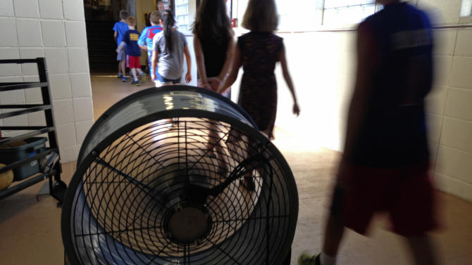 In this Wednesday, Aug. 28, 2013 photo, students at Washington Elementary School in Monticello, Ill., walk past a large fan used to help cool the school. The school, built in 1894, has air conditioning in only a few spots and has been sending students home early this new school year as temperatures push into the 90s every day. (AP Photo/David Mercer)