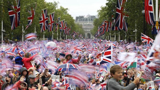 """FILE - In this June 5, 2012 file photo revelers on the Mall in London watch Britain Queen Elizabeth II appear on the Buckingham Palace balcony as part of a four-day Diamond Jubilee celebration to mark the 60th anniversary of  Queen Elizabeth II accession to the throne. The British government is revising the """"Life in the U.K."""" handbook and test taken by those seeking to settle in Britain. While the previous version contained some practical questions about daily life, the emphasis is now on British history and culture. There are questions on sports, music and historical figures from William Shakespeare to Winston Churchill. The government says the new handbook, published Monday Jan. 28, 2012, also features """"an exploration of Britons' unique sense of humor and satire."""" (AP Photo/Sang Tan, File)"""