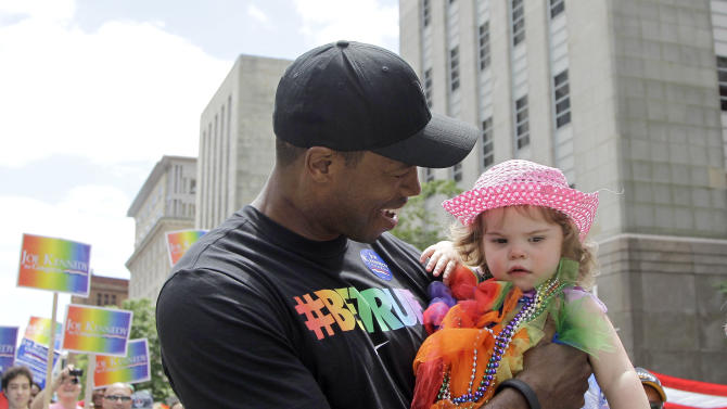 NBA veteran Jason Collins, the first active player in one of four major U.S. professional sports leagues to come out as gay, holds 19-month-old Evangeline Salzberg, of Bellingham, Mass., as he walks in Boston's gay pride parade, Saturday, June 8, 2013, in Boston. (AP Photo/Mary Schwalm)