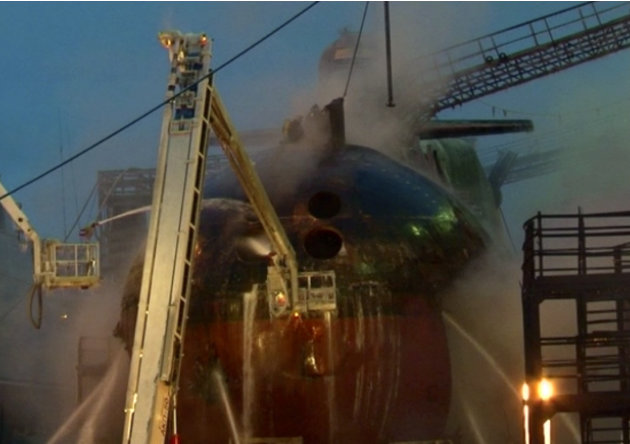 In this video image from Ru-RTR Russian state channel, firefighters spray water on the Yekaterinburg nuclear submarine in a dock at the Roslyakovo shipyard in the Murmansk region, Russia, Friday, Dec.