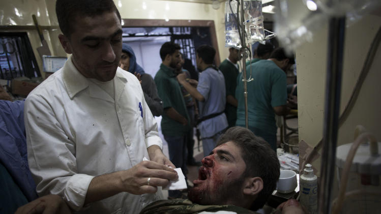 In this Saturday, Oct. 13, 2012 photo, a Syrian doctor treats a wounded Free Syrian Army fighter at Dar al-Shifa hospital in Aleppo, Syria. (AP Photo/ Manu Brabo)