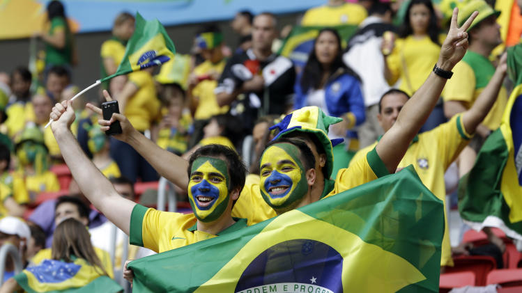 Brazil fans smile prior to the group A World Cup soccer match between Cameroon and Brazil at the Estadio Nacional in Brasilia, Brazil, Monday, June 23, 2014. (AP Photo/Andre Penner)