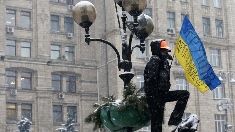 A pro-European integration protester stands on top of a pile of debris at Independence Square in Kiev