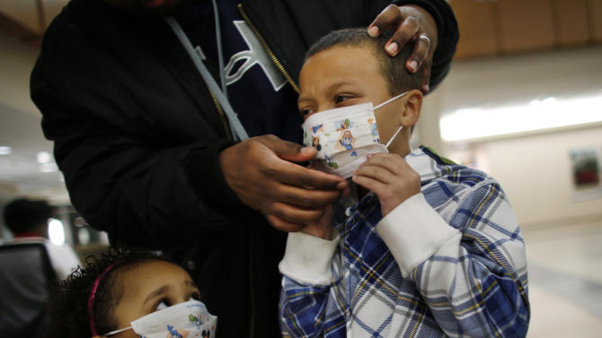 FILE - In this Wednesday, Jan. 9, 2013 file photo, Damien Dancy puts masks on his children Damaya, 3, left, and Damien, 7, at Sentara Princess Anne Hospital in Virginia Beach, Va., as hospitals in Hampton Roads are urging patients and visitors to wear a mask at their facilities to help stop the spread of the flu. Health officials say nine more deaths of children from the flu have been reported, bringing the total this flu season to 29. In a typical season, about 100 children die of the flu, so it is not known whether this year will be better or worse than usual. The Centers for Disease Control and Prevention says half of confirmed flu cases so far are in people 65 and older. (AP Photo/The Virginian-Pilot, Stephen M. Katz, File)