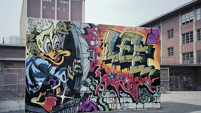 """In this 1978 photo provided by the Museum of the City of New York, the graffiti mural """"Howard the Duck,"""" is painted on a handball court in New York. The Lee Quinones mural was a pivotal work that helped propel the illicit graffiti art movement from the subway system to above ground, and into the mainstream. The original mural has been painted over, but Quinones recreated it on canvas and it is part of the exhibition, """"City as Canvas."""" (AP Photo/Charlie Ahearn)"""