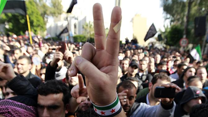 An anti-Syrian regime protester flashes the victory sign with a Syrian revolutionary flag bracelet as he listen to Sheik Ahmad al-Assir, unseen, a hardline Sunni Lebanese cleric, deliver a sermon in support of Syrian rebel fighters and Syrian refugees, after Friday prayer, in Beirut, Lebanon, Friday, Feb. 8, 2013. Al-Assir, like many other Sunni Muslim clerics in Lebanon, has been vocal in speaking out against the Syrian regime and its allies in Lebanon. (AP Photo/Bilal Hussein)