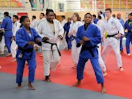 Cuban judokas warm up with French judokas of a local team at a training camp in Wasquehal, northern France on July 19