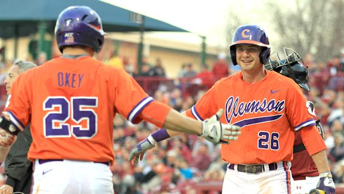 Clemson's Chris Okey, left, celebrates with Reed Rohlman after Rohlman scored during an NCAA college baseball game against South Carolina at Carolina Stadium in Columbia, S.C., on Monday, Mar. 2, 2015. (AP Photo/Anderson Independent-Mail, Mark Crammer)