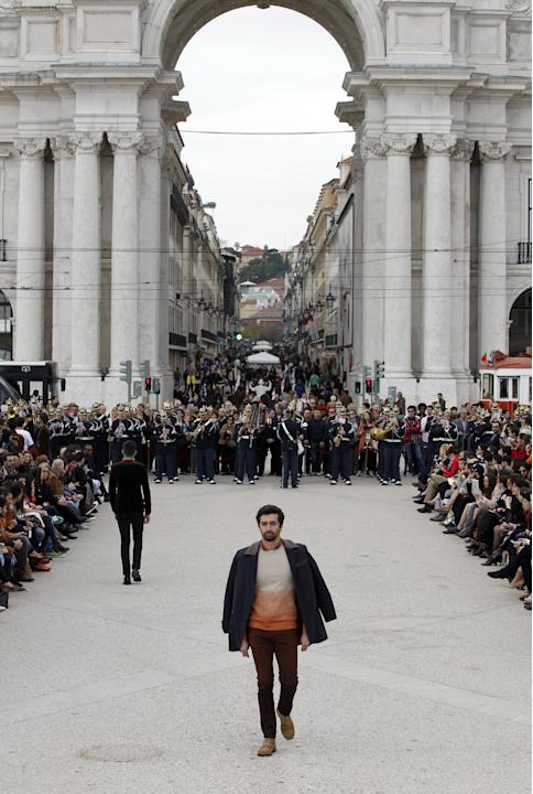 Models wear creations by Portuguese designer Nuno Gama at Lisbon's Comercio square during the ModaLisboa fashion week, in Portugal Sunday, March 9, 2014. (AP Photo/Francisco Seco)
