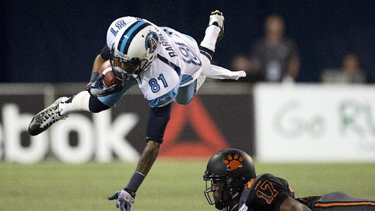 10ThingstoSeeSports - Toronto Argonauts wide receiver Jason Barnes (81) is upended by B.C. Lions half back T. J. Lee during first half CFL football action in Toronto on Sunday, Aug. 17, 2014