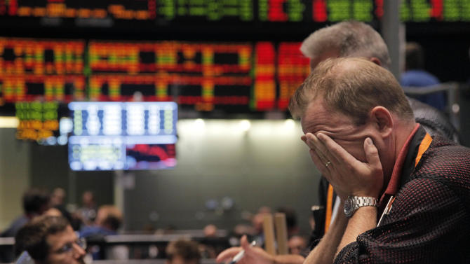 Trader Andrew Stavros reacts after the close of trading in the NASDAQ, 100 Index pit, on the floor of The CME Group Monday, Aug. 8, 2011, in Chicago. Stocks plummeted at the close after anxiety overtook investors on the first trading day since Standard & Poor's downgraded American debt. (AP Photo/M. Spencer Green)