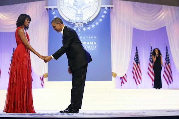 President Barack Obama bows as he and first lady Michelle Obama, wearing a ruby colored chiffon and velvet Jason Wu gown, gets ready to dance as singer Jennifer Hudson, right, sings Al Green's &quot;Let's 