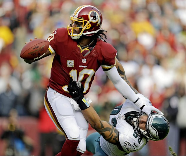 Washington Redskins quarterback Robert Griffin III pushes Philadelphia Eagles defensive end Jason Babin away as he looks to get rid of the ball during the first half of an NFL football game in Landove