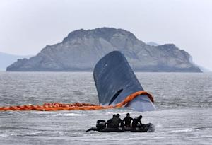 "Vessel involved in salvage operations passes near the upturned South Korean ferry ""Sewol"" in the sea off Jindo"