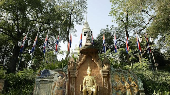 In this photo taken, Feb. 25, 2013, the statue of former King Sisowath, center, is displayed at Wat Phnom, in Phnom Penh, Cambodia. With a pricetag of a dollar, admission to the centuries-old hilltop temple of Wat Phnom isn't quite free. Nor are the elephant rides that are offered on site. But a free and carefree stroll along the bucolic grounds is a reward in and of itself. Sculpted into the hillside leading to the temple's entrance is a functioning topiary clock, whereas the gigantic sculpture of a Naga, or sea snake, provides yet another photo op. (AP Photo/Heng Sinith)