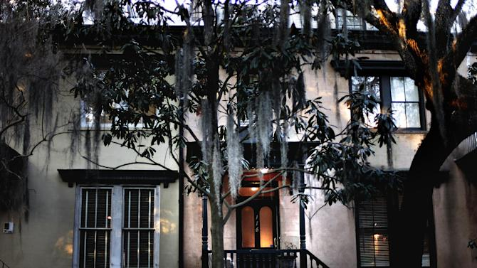 In this Feb. 21, 2011 photo, a front door is illuminated at dusk in the historic district of Savannah, Ga. A proposal to roll out double-decker buses on the streets of historic downtown Savannah has residents complaining the change would amount to a tourism overload. Two Boston businessmen are lobbying Savannah City Hall to end a 17-year ban on double-decker buses in the downtown historic district of Georgia's oldest city. The city's Downtown Neighborhood Association is opposing the change. Its members say the buses would risk collisions with low-hanging tree limbs and would turn passengers into Peeping Toms capable of peering into second-story windows. (AP Photo/David Goldman)