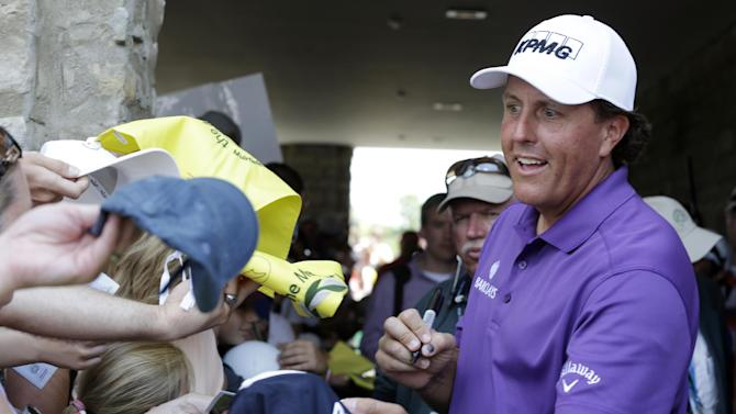 Phil Mickelson signs autographs for fans following his third round of the Memorial golf tournament Saturday, May 31, 2014, in Dublin, Ohio. (AP Photo/Darron Cummings)