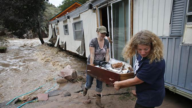 """FILE - In this Sept. 13, 2013 file photo, water rushes through her destroyed home as resident Holly Robb, left, and her neighbor Pam Bowers salvage belongings after storms that raged through the Rocky Mountain foothills in this photo made in Lyons, Colo. Two low-lying trailer parks in the small town, 20 minutes to the north of Boulder, bore the brunt of the recent flooding. """"I don't think we'll ever be able to go back,"""" said Robb. (AP Photo/Brennan Linsley, File)"""