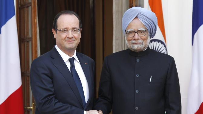 France's President Hollande shakes hands with India's PM Singh during a photo opportunity before their meeting in New Delhi