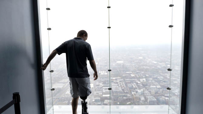 "Zac Vawter, fitted with an experimental ""bionic"" leg, looks out onto the Ledge at the Willis Tower, Thursday, Oct. 25, 2012 in Chicago. Vawter is training for the world's tallest stair-climbing event where he'll attempt to climb 103 flights to the top of the Willis Tower using the new prosthesis.  Vawter will put his bionic leg to the ultimate test Sunday, Nov. 4,  when he attempts to climb 103 flights of stairs to the top of Chicago's Willis Tower, one of the world's tallest skyscrapers. If all goes well, he'll make history with the bionic leg's public debut.  (AP Photo/Brian Kersey)"