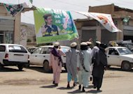 Pakistani armed tribesmen walk past electoral posters at a market in Miranshah, the capital of North Waziristan tribal area on May 8, 2013. Women were stopped from voting in Pakistan's elections on Saturday in the northwestern tribal district of North Waziristan, a notorious Taliban stronghold, residents said