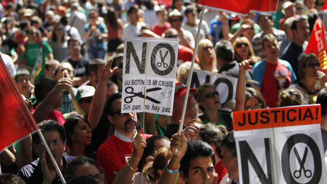 """People hold up banners reading """"their fortune, our crisis"""", """"no food, no peace"""" and """"no cuts!, justice"""" during a protest against austerity measures applied by the Spanish government in  olumbus Square, Madrid, Spain, Saturday, Sept. 15, 2012. Tens of thousands of people from all over the country converged on Madrid to hold a large anti-austerity demonstration on Saturday. (AP Photo/Andres Kudacki)"""