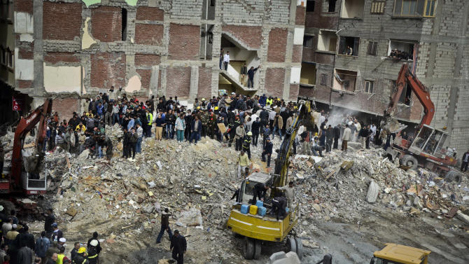 Egyptians stand in rubble after an eight story building collapsed in Alexandria, Egypt, Wednesday, Jan. 16, 2013. Egypt's official MENA news agency says two people have been killed. It was not immediately known what caused the building to collapse, but violations of building specifications have been blamed in the past for similar accidents. (AP Photo)