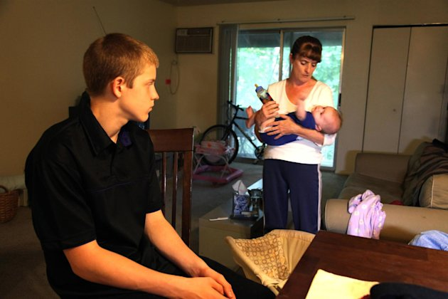 In this Sept. 16, 2011 photo, Kris Fallon holds her 4-month-old daughter Addison, in Palatine, Ill., as her 15-year-old son Gared Fallon looks on. The Fallon family has been living in poverty for near