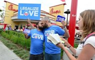 "A couple kiss in front of a Chick-fil-A fast food restaurant in Hollywood as a Christian activist reads passages from the Bible on August 3, in Hollywood, California. Gays and lesbians puckered up in protest Friday, staging ""kiss-ins"" outside Chick-fil-A outlets across the United States over the fast food chain's opposition to same-sex marriage"