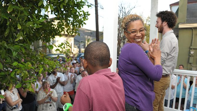 FILE - In this March 1, 2012, file photo homeowner Mary Jones celebrates with her 10-year-old son Paul Williams during a dedication for their newly renovated home in New Orleans. Nearly two dozen volunteers from Rebuild Joplin, Mo., traveled to New Orleans to work with a group that renovates Katrina-damaged homes in a partnership that could change the way other American cities both plan for and recover from the next blow by nature's fury. (AP Photo/Cheryl Gerber, File)