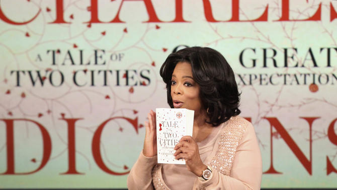 """This photo taken Nov. 19, 2010 in Chicago and provided by Harpo Productions Inc., shows talk-show host Oprah Winfrey announcing on """"The Oprah Winfrey Show"""" airing, Monday, Dec. 6, 2010, her book club selections, """"A Tale of Two Cities"""" and """"Great Expectations"""" by Charles Dickens. (AP Photo/Harpo Productions Inc., George Burns)  NO SALES"""