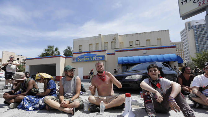 """A few demonstrators sit on a Domino's Pizza parking lot in protest, Thursday, Aug. 30, 2012, in Tampa, Fla. The three dozen chanting anti-GOP protesters hit a lull of silence as they marched through a neighborhood of low-income housing in west Tampa. """"What are you guys doing taking a nap?"""" shouted one protester to his cohorts. Another shouted, """"You guys are reeeeaaal quiet, now!"""" The protests against the Republican convention in Tampa have been unexpectedly muted this week, something even the protesters acknowledge. (AP Photo/Chris O'Meara)"""